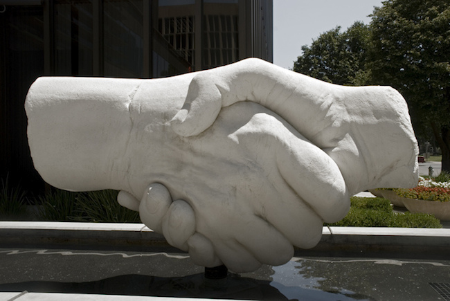 large concrete sculpture of two hands shaking