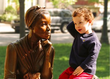 image of boy talking to a statue